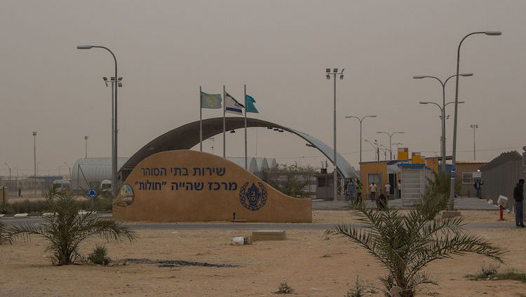 Photo: The entrance to Holot immigration detention centre, Negev desert, Israel. Credit: Wikimedia Commons.