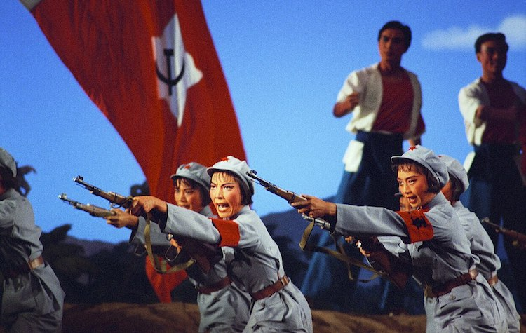 Photo: A scene from The Red Detachment of Women opera, adopted from the earlier 1961 film of the same title. Soldiers of the Women's Detachment performing rifle drill in Act II, from the 1972 National Ballet of China production. Source: Wikimedia Commons.