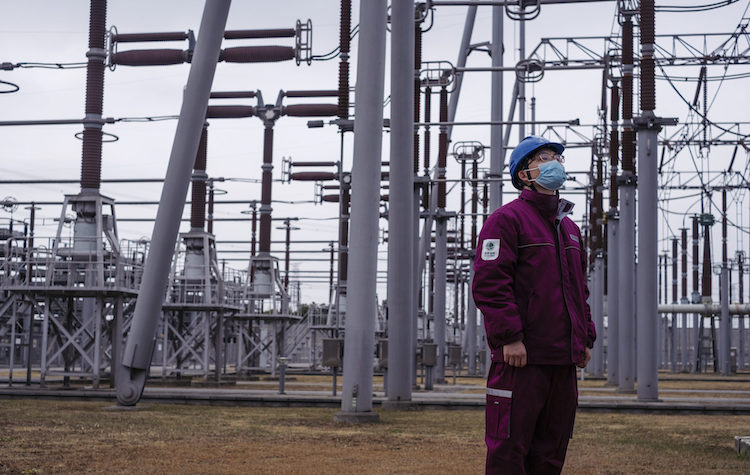 Photo: Zhang Dezhen, a staff member at the Shanghai Fengxian Converter Station, patrols the power converter area. Credit: Wu Huiyuan/Sixth Tone.