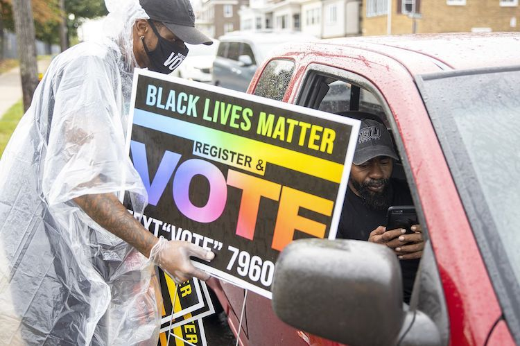 Photo: Damien Grobes, 42, of West Philadelphia, lead manager for One Pennsylvania, helps a man driving by to text their number and hands them a sign to help others register to vote in North Philadelphia, on September 26. Credit: TYGER WILLIAMS / The Philadelphia Inquirer