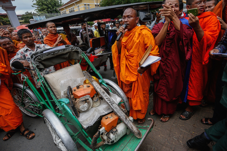 Photo: But Buntenh speaks outside the Forestry Administration's headquarters in Phnom Penh last year as monks display chainsaws seized from illegal loggers in the Prey Lang forest. Courtesy: Siv Channa | The Cambodia Daily
