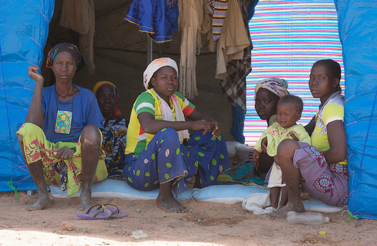 Photo: Family members who have fled conflict sit inside their tent at the Pissila camp for displaced people in Burkina Faso. WFP/Marwa Awad
