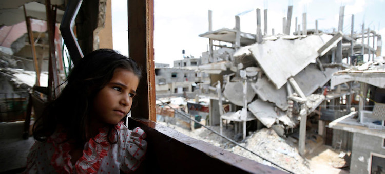 Photo: A Palestinian girl inside her family's partially destroyed home, looks at the destruction outside, in the Shejaiya neighbourhood of Gaza City. Credit: UNICEF.