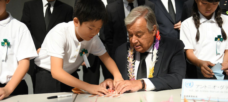 Photo: Secretary-General António Guterres folds origami cranes with young Japanese leaders at the Nagasaki Peace Memorial. Credit: Dan Powell | UN Photo.