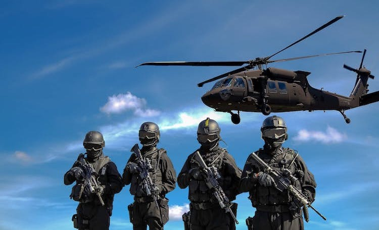 Photo: Four soldiers carrying rifles near helicopter under blue sky. Credit: Somchai Kongkamsri