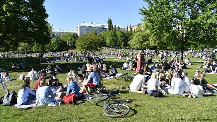Photo: People in a Park in Stockholm without observing social distancing. Images / H. Credit: Imago Images/H. Montgomery. Source: The Coversation.
