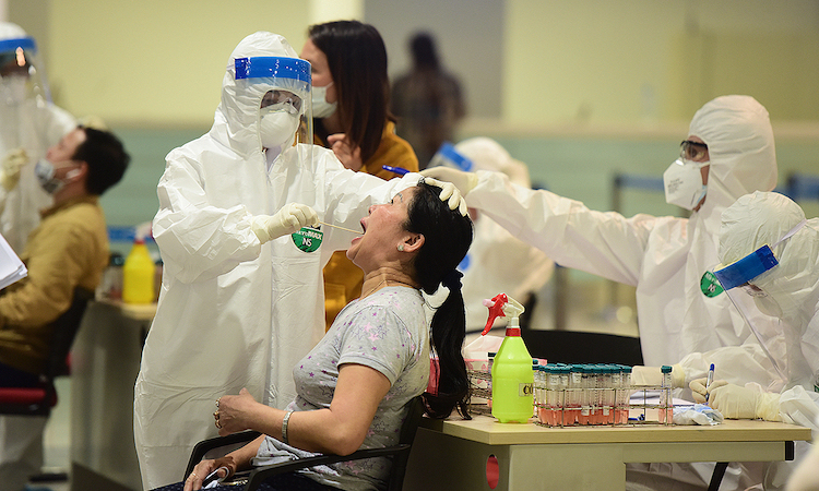 Photo: A woman has her samples taken for COVID-19 testing upon arriving at Noi Bai International Airport, Hanoi, March 18, 2020. Credit: VnExpress/Giang Huy.